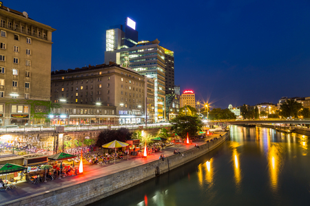 blue hour: VIENNA, AUSTRIA - 21ST AUGUST 2015: A view along the Danube Canal during the blue hour. People, buildings and bars can be seen. Editorial
