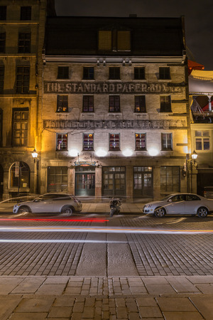 commune: MONTREAL, CANADA - 17TH MAY 2015: A view of buildings along Rue de la Commune in Old Montreal at night.