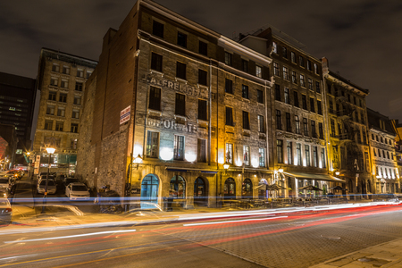 commune: MONTREAL, CANADA - 17TH MAY 2015: A view of buildings along Rue de la Commune in Old Montreal at night. The trails of traffic can be seen.
