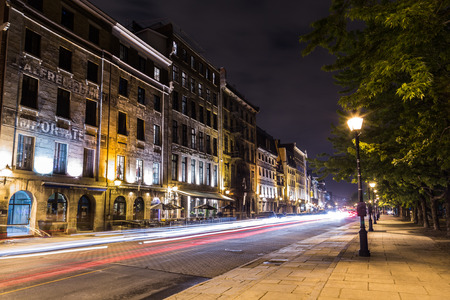 cobbled: MONTREAL, CANADA - 17TH MAY 2015: A view of buildings along Rue de la Commune in Old Montreal at night. The trails of traffic can be seen.