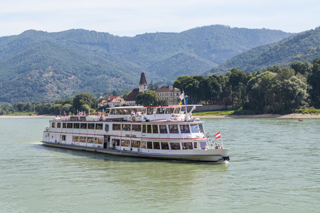 boat: KREMS, AUSTRIA - 28TH AUGUST 2015: A Large passenger boat in the Danube River during the summer. Lots of people can be seen on the boat.