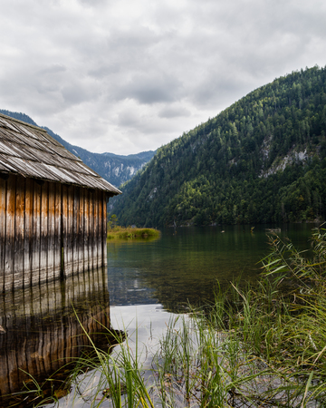 boat house: A lake and an old boat house at a lake in Austria. Hills can be seen in the distance