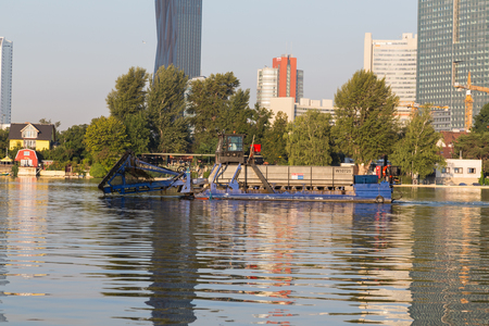 skim: VIENNA, AUSTRIA - 1ST SEPTEMBER 2015: A large industrial boat in the water in Vienna during the morning.