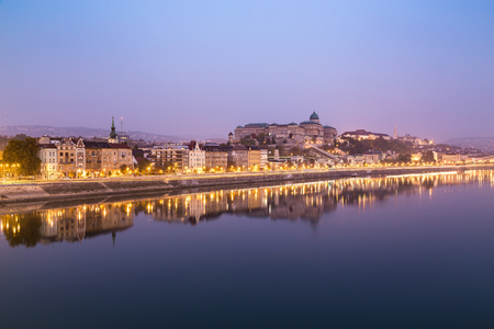 friedrich: A view along Friedrich Born Rakpart in Budapest in the early morning, showing buildings, reflections and in the distance the Buda Castle