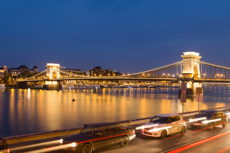 chain bridge: BUDAPEST, HUNGARY - 29TH OCTOBER 2015: The Szechenyi Chain Bridge in Budapest Hungary from the distance at night. Cars can be seen in the foreground. Editorial