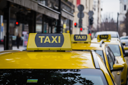 taxi sign: buDAPEST, HUNGARY - 29TH OCTOBER 2015: Signs for yellow Taxis parked on a street in Budapest during the day.