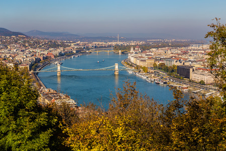 chain bridge: High angle view of Budapest during the day in the autumn. Parliament, the Chain Bridge, buildings and boats can be seen.