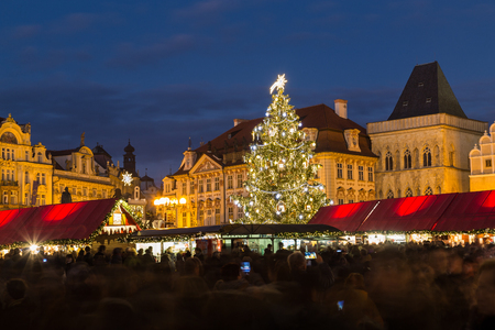 town square: PRAGUE, CZECH REPUBLIC - 6TH DECEMBER 2015: The Christmas Tree and Market Stalls at Prague Old Town Square at Christmas. Large amounts of people can be seen.