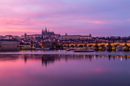 Charles Bridge in Prague, towards the Lesser Quarter and Prague Castle at sunset with a colorful vibrant sky.