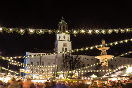 residenz: SALBURG, AUSTRIA - 11TH DECEMBER 2015: Decorations and the Neue Residenz at Salzburg Christmas Market in the Residenzplatz area at night.  People can be seen. Editorial