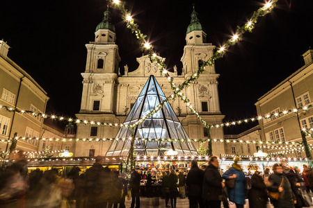 christkindlmarkt: SALBURG, AUSTRIA - 11TH DECEMBER 2015: Decorations and buildings at Salzburg Christmas Market in the Domplatz area at night. People can be seen.