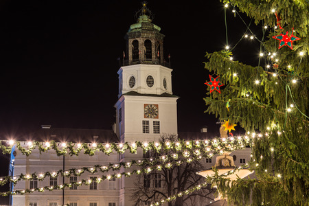 residenz: SALBURG, AUSTRIA - 11TH DECEMBER 2015: Christmas decorations, the tree and the Neue Residenz Clock Tower at Salzburg Christmas Market in the Residenzplatz area at night.