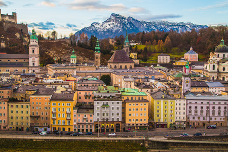 bienes raices: SALZBURG, AUSTRIA 12TH DECEMBER 2015: A high view of buildings and churches in Salzburg during the day showing the colourful exteriors. Mountains can be seen in the distance,.