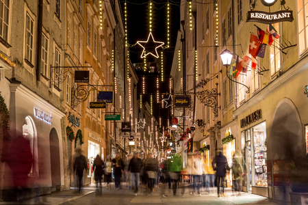 shop sign: SALBURG, AUSTRIA - 11TH DECEMBER 2015: A view along Getreidegasse in Salzburg at night during the Christmas season. People, shops and buildings can be seen.