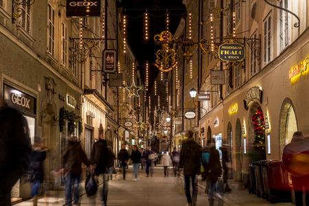 Salburg, AUSTRIA - 11 de diciembre de 2015: Una vista a lo largo Getreidegasse en Salzburgo en la noche durante la temporada de Navidad. Personas, tiendas y edificios se pueden ver.