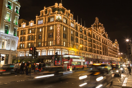 harrods: LONDON, UK - 23RD DECEMBER 2015: The outside of Harrods Department Store in London at night during the Christmas Season. People and traffic can be seen.