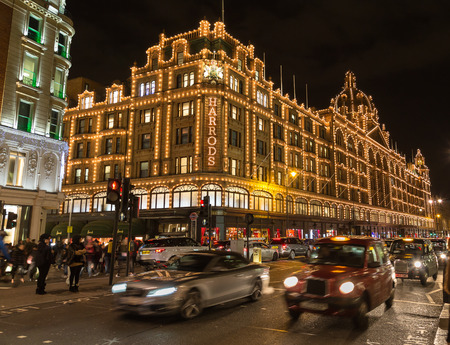 knightsbridge: LONDON, UK - 23RD DECEMBER 2015: The outside of Harrods Department Store in London at night during the Christmas Season. People and traffic can be seen.