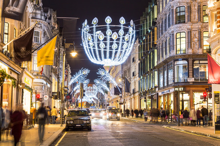 LONDON, UK - 23RD DECEMBER 2015: A view down New Bond Street in London during the Christmas period showing building exteriors, decorations, people and traffic. Editorial