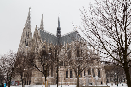 innere: VIENNA, AUSTRIA - 5TH JANUARY 2016: The outside of the Votive Church in Vienna during the day during the winter with lots of snow. People can be seen.