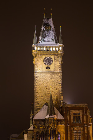 old town hall: A view of the Old Town Hall Clock Tower in Prague at Night in the Winter. Snow can be seen on the roof. Stock Photo