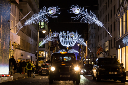 bond street: LONDON, UK - 30TH DECEMBER 2015: A view along New Bond Street in London at Christmas showing decorations, traffic and people