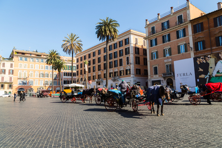 spanish steps: ROME, ITALY - 12TH MARCH 2015: Horse and Carriages near the Spanish Steps in Rome during the day. People can be seen.