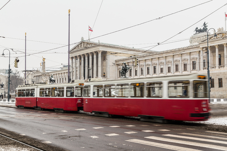 innere: VIENNA, AUSTRIA - 5TH JANUARY 2016: Old trams and traffic outside the Austrian Parliament building in Vienna during the winter months.