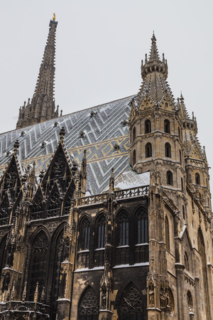 innere: A low view of St. Stephens Cathedral (Stephansdom) at Stephansplatz in Vienna during the winter. Snow can be seen on the building.