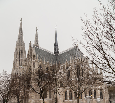 innere: The outside of the Votive Church in Vienna during the day during the winter with lots of snow. People can be seen.