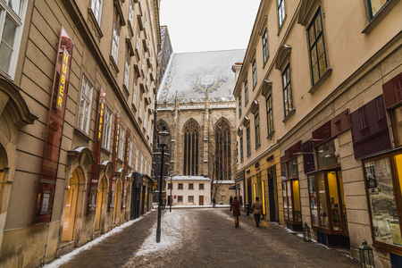 innere: VIENNA, AUSTRIA - 5TH JANUARY 2016: Part of St. Stephens Cathedral (Stephansdom) in Vienna from Churhausgasse during the winter. Snow can be seen on the building. People can be seen.