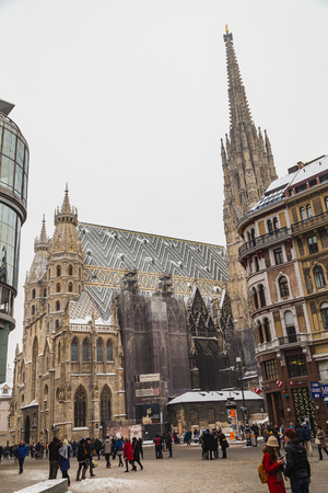 stephansplatz: VIENNA, AUSTRIA - 5TH JANUARY 2016: A low view of St. Stephens Cathedral (Stephansdom) and Stephansplatz in Vienna during the winter. Snow can be seen on the building. People can be seen. Editorial