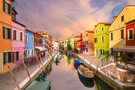 A view of colourful houses in Burano during the day along the canal. Colourful clouds can be seen in the sky.