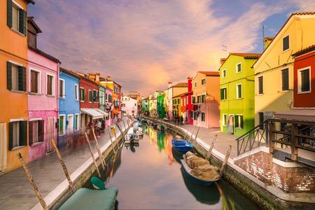 Une vue de maisons colorées de Burano pendant la journée le long du canal. nuages ??colorés peuvent être vus dans le ciel.