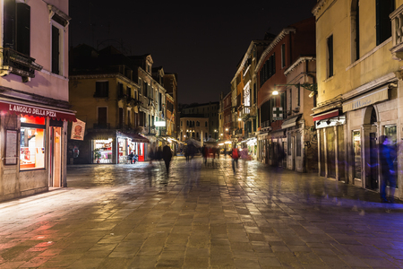 VENICE, ITALY - 13TH MARCH 2015: Buildings and businesses along Rio Terà S. Leonardo in Venice at night. The blur of people walking can be seen. Editorial