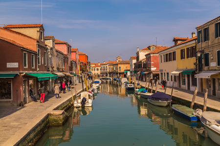 MURANO, ITALY - 14TH MARCH 2015: A view along Fondamenta Dei Vetrai and Fondamenta Daniele Manin footpaths in Murano during the day, showing shops, boats, buildings and people