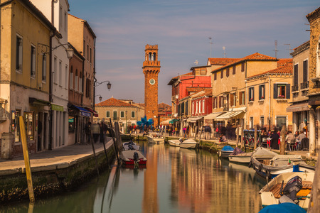 manin: MURANO, ITALY - 14TH MARCH 2015: A view along streets in Murano with the bell tower in the background. People can be seen along the paths.