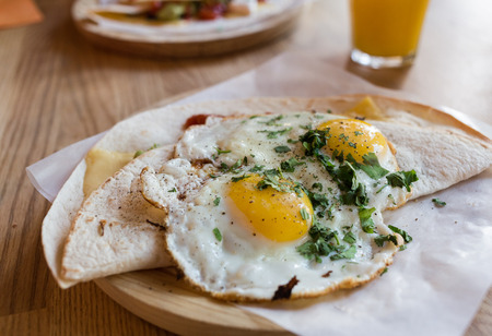 tortilla wrap: Fried eggs on a folded  tortilla  wrap with fresh seasoning. Served on a wooden plate and baking paper.