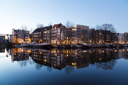 dutch canal house: A view along the Oudeschans Canal in Amsterdam at twilight.