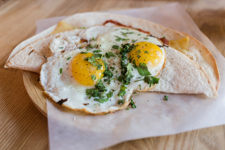 eg: Fried eggs on a folded  tortilla  wrap with fresh seasoning. Served on a wooden plate and baking paper.