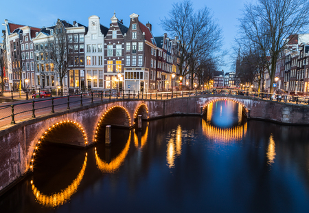 dutch canal house: A view of the bridges at the Leidsegracht and Keizersgracht canals intersection in Amsterdam at dusk.