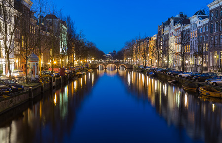 dutch canal house: AMSTERDAM, NETHERLANDS - 16TH FEBRUARY 2016: A view along the Keizersgracht canal in Amsterdam at night. Reflections, buildings and cars can be seen.