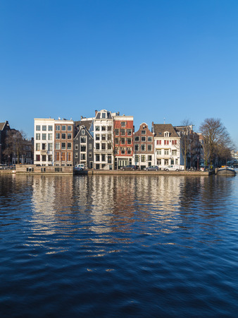 canal street: AMSTERDAM, NETHERLANDS - 17TH FEBRUARY 2016: Buildings along Staalkade street in Amsterdam. Part of the Amstel canal can be seen.