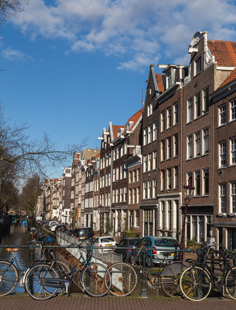 decorated bike: AMSTERDAM, NETHERLANDS - 16TH FEBRUARY 2016: A view of buildings along the Amsterdam canals and bicyles chained to the railings.