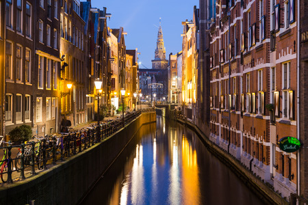 dutch canal house: AMSTERDAM, NETHERLANDS - 17TH FEBRUARY 2016: A view along Oudezijds Kolk canal in Amsterdam at night. Buildings, bikes and the top of The Oude Church can be seen.