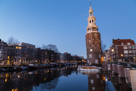 dutch canal house: A view along the Oudeschans Canal towards the Montelbaanstoren Tower in Amsterdam at twilight. Stock Photo