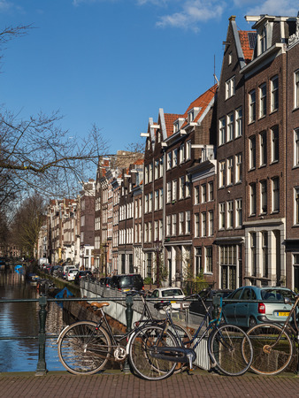 dutch canal house: AMSTERDAM, NETHERLANDS - 16TH FEBRUARY 2016: A view of buildings along the Amsterdam canals and bicyles chained to the railings.