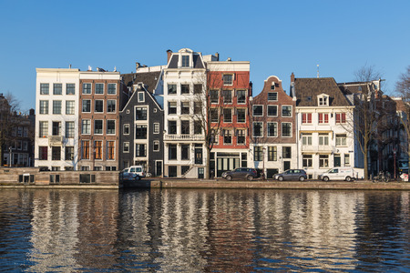 amstel: AMSTERDAM, NETHERLANDS - 17TH FEBRUARY 2016: Buildings along Staalkade street in Amsterdam. Part of the Amstel canal can be seen.