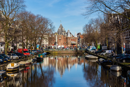 amsterdam: AMSTERDAM, NETHERLANDS - 16TH FEBRUARY 2016: A view towards The Waag (weigh house)  in Amsterdam from the Kloveniersburgwal canal. People, cars, bikes and other buildings can be seen. Editorial