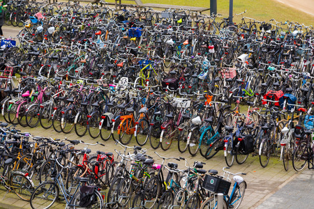 parked bikes: AMSTERDAM, NETHERLANDS - 18TH FEBRUARY 2016: Large amounts of bikes parked at a bike rack in Amsterdam