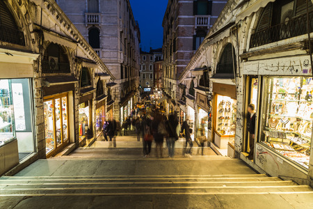 rialto bridge: VENICE, ITALY - 14TH MARCH 2015: A view of shops and streets along Rialto Bridge at night. The blur of people can be seen.